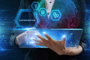 Person in Business-Kleidung hält und bedient Tablet, Schlagwort CUSTOMIZATION, angedeutete Vernetzung von Daten in Hologram-Optik