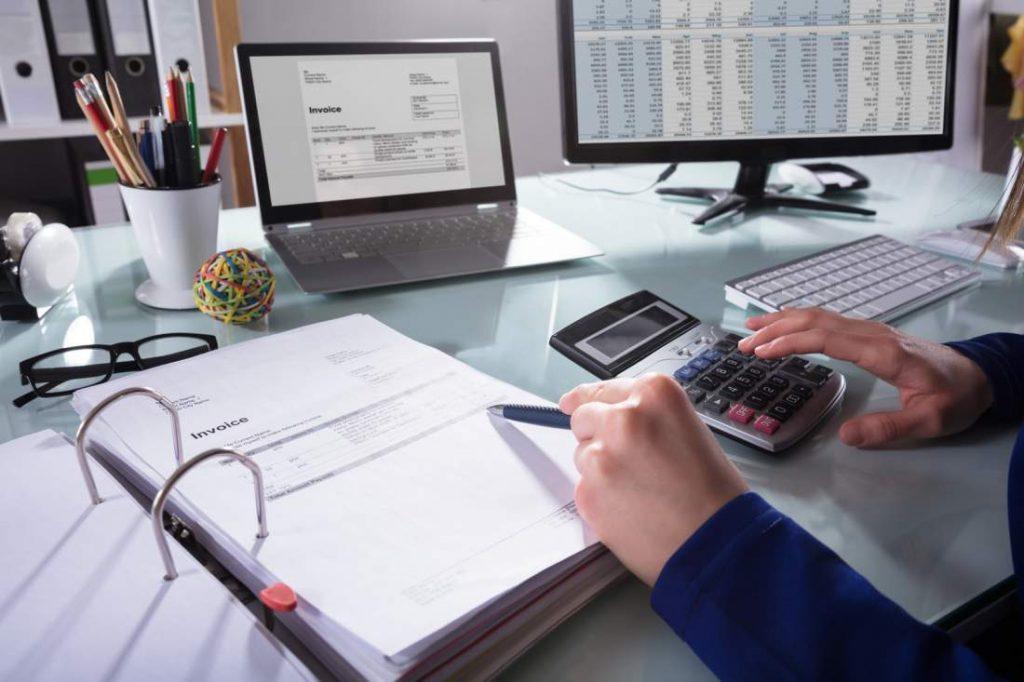 Schreibtisch, Monitor, Bildschirm, Ordner, Unterlagen, Dokumente, Taschenrechner, Stift, Berechnungen, Kalkulationen, Verrentungsprozess, Software-Automatisierung, Robotic Process Automation, RPA, Kosten-Nutzen-Analyse, Digitalisierung