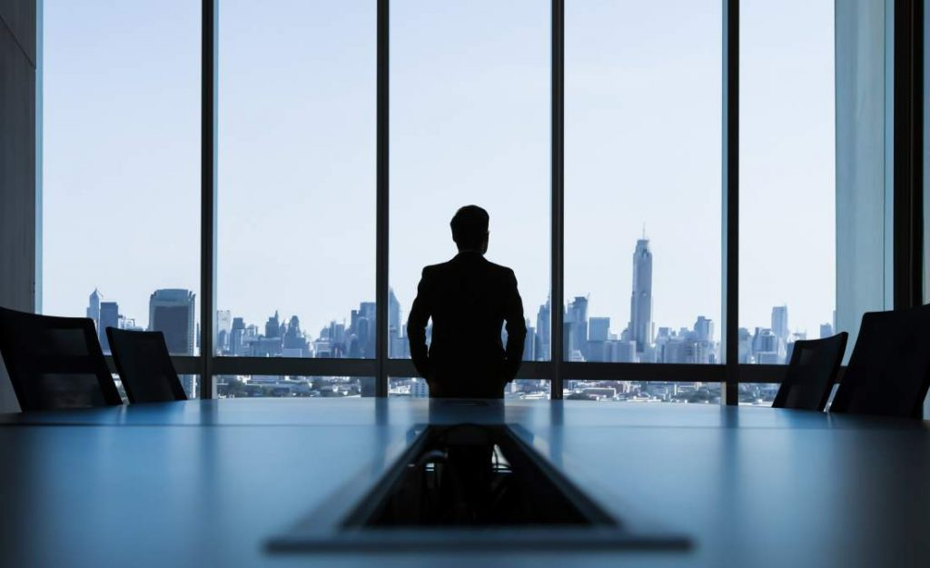 Geschäftsführung, Management, Manager vor Glasfenster, Meeting-Raum, Zukunftsvision, Unternehmensführung im Wandel der Zeiten, Unternehmensleitung, Unternehmenssteuerung, Zukunftsfähigkeit von Unternehmen