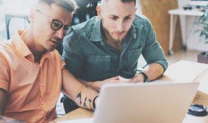 Zwei Männer sitzen vor dem Geschäftslaptop zur Datenauswertung und Entscheidungsfindung im Start-up