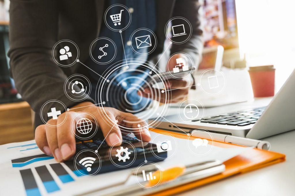 Geschäftsmann mit verschiedenen digitalen Geräten und vernetzten Kanälen am Schreibtisch