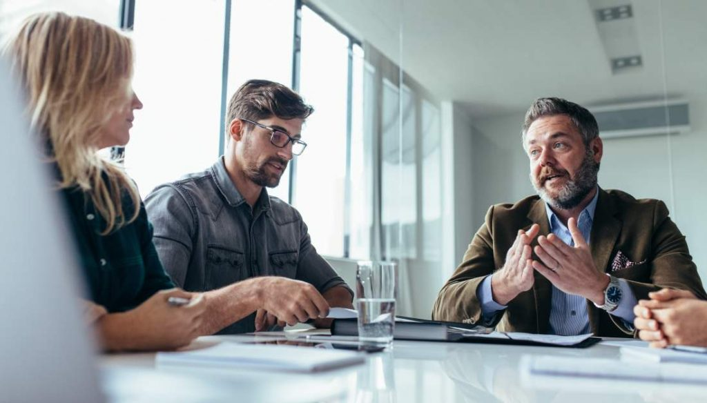 Zwei Geschäftsmänner und eine Geschäftsfrau sprechen über ein unternehmensrelevantes THema, Mann mit Bart im raunen Sakko mit erklärender Gestik