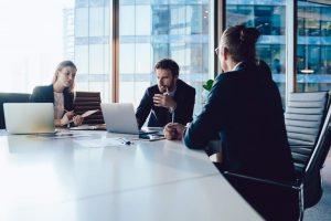 Ernste Geschäftsleute in Meetingraum vor Laptops, einer der Geschäftsmänner sieht wütend und genervt aus aufgrund dessen, was er auf dem Bildschirm sieht