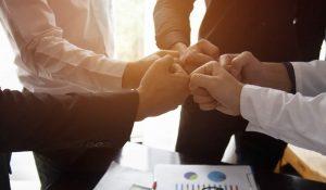 Geschäftsmenschen Fistbump bei Meeting über Tisch mit Unterlagen