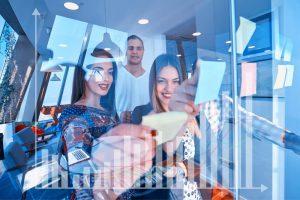 Junge Frauen und Männer in agilem Unternehmen mit guter Laune an Post-its an Glaswand