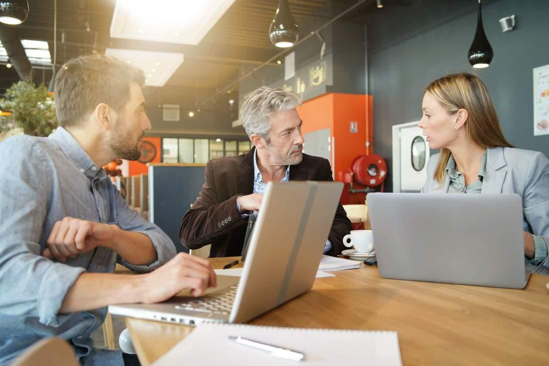 Drei Führungskräfte im Austausch mit Laptops am Tisch