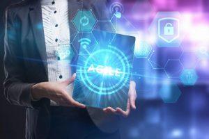 Geschäftsfrau hält Tablet in die Mitte des Bildes mit dem Schriftzug AGILE, vernetzt mit technischen Icons für Geschäftsmodelle, Internet als futuristische Darstellung für agile und digitale Transformation