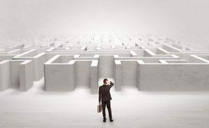 Geschäftsmann mit Aktenkoffer steht ratlos einem Labyrinth gegenüber