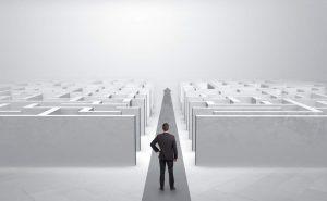 Geschäftsmann steht vor einem Labyrinth, durch das ein gangbarer Weg wie eine Schneise hindurchführt