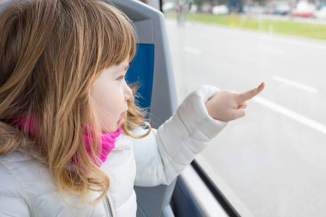 Kleines Kind in öffentlichem Verkehrsmittel blickt durch das Fenster und deutet auf etwas draußen