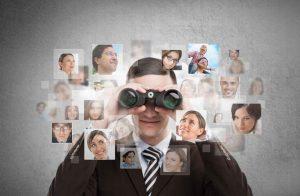 Geschäftsmann mit Fernglas schaut auf Profilbilder von Teammitgliedern