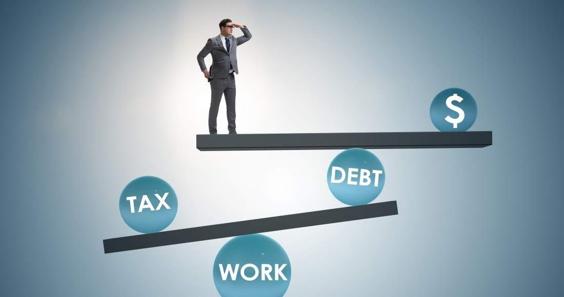Geschäftsmann steht auf der Kippe/Wippe mit Geld, Steuern, Schulden und Arbeitslast (Symbolbild)
