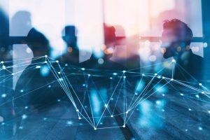 Menschensilhouetten in digital wirkenden Blautönen, im Vordergrund engedeutete Datenvernetzung