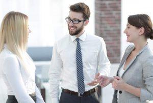 Geschäftsmann und zwei Geschäftsfrauen im Gespräch in hellem Büroraum