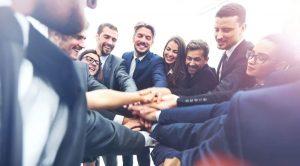 Team von Geschäftsmenschen stehen eng im Kreis zusammen und legen die Hände aufeinander in einer Geste des Zusammenhalts