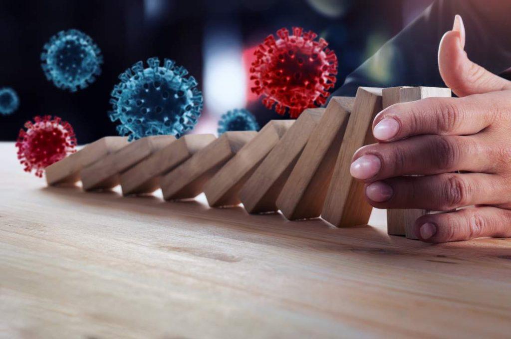 Corona-Viren bringen Domino-Steine zu Fall, Geschäftsfrau hält die Kettenreaktion mit ihrer Hand auf
