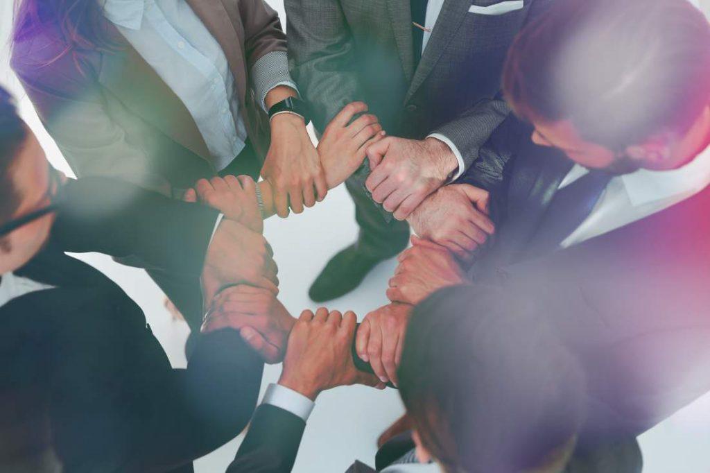 Team von Geschäftsmenschen in Business-Kleidung eng im Kreis zusammen und halten das Handgelenk der jeweils nächsten Person in einer Geste des Zusammenhalts