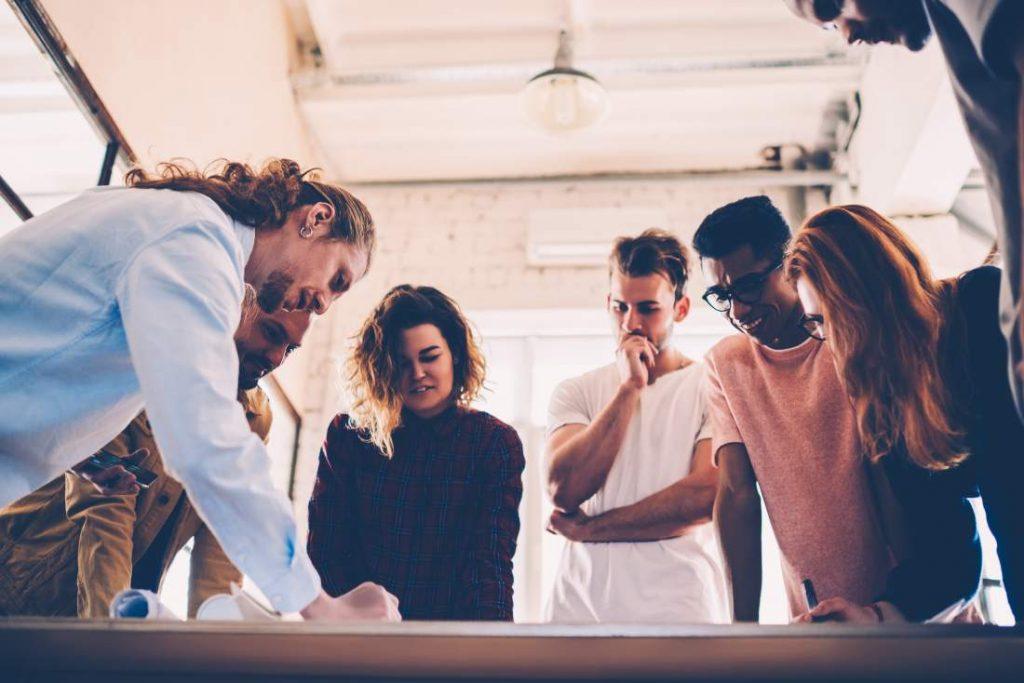 Junges Team in Meeting steht um einen Tisch herum und bespricht konzentriert einen Plan