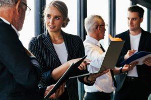 Diverse Geschäftsmenschen stehen vor raumhohen Fenstern in Meetingraum und diskutieren in Einzelgesprächen