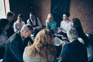 Mitarbeitende sitzen im Kreis zusammen und führen Einzelgespräche