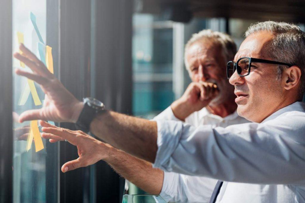 Zwei Geschäftsmänner vor Glasscheibe mit Klebezettel besprechen Unternehmensprozesse