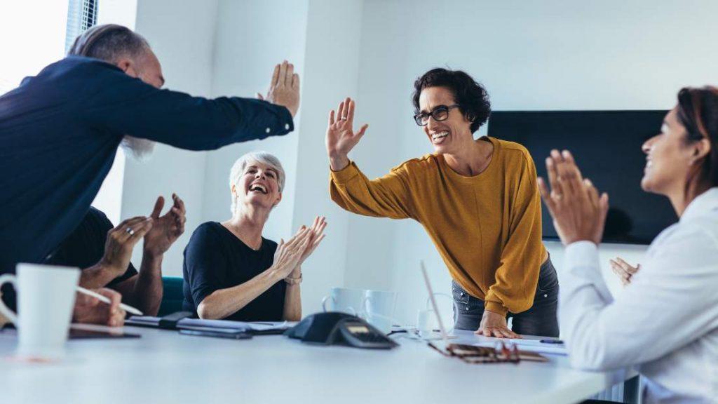 Team in Meetingraum applaudiert und klatscht ab zum unternehmerischen Erfolg