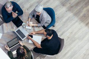 Team in einem Business Strategie-Meeting an einem Holztisch, Vogelperspektive