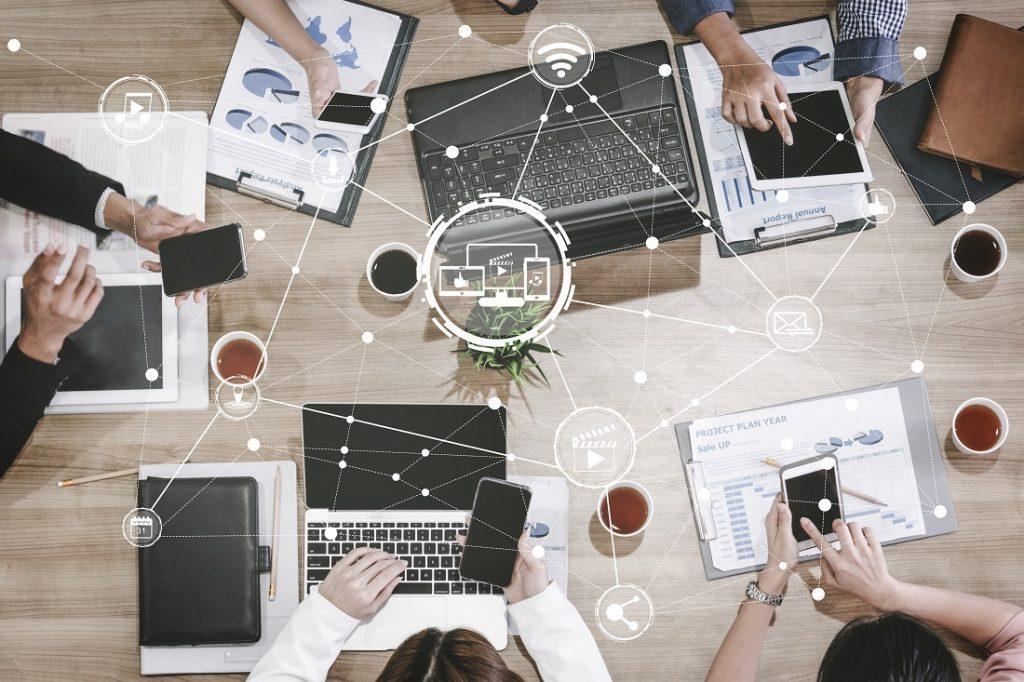 Mitarbeiter sichten Dokumente mithilfe vernetzter Geräte am Konferenztisch