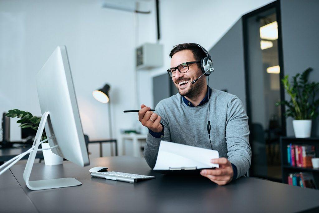 Lächelnder Help-Desk-Mitarbeiter am Telefon