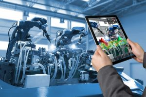 Hände halten ein Tablet, auf dem die Maschine im Bildhintergrund zu sehen ist, auf dem Tablet jedoch mit farbigen Markierungen und Optionen
