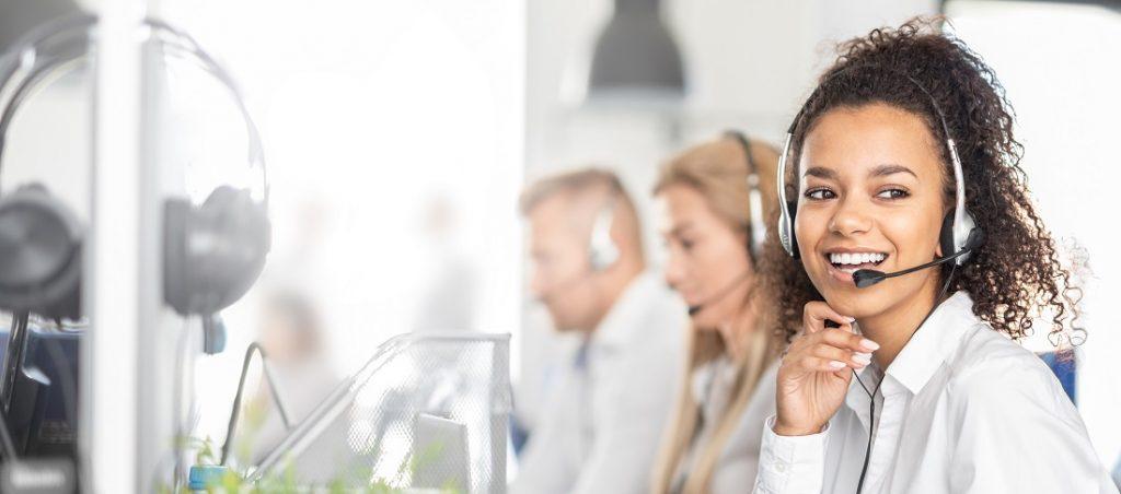 Lächelnde Frau im Call-Center beraet Kunden