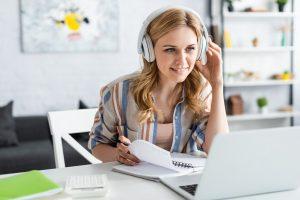Frau mit Kopfhoerern vor Laptop bei E-Learning