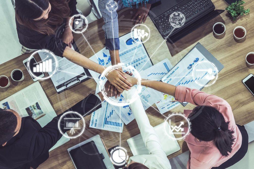 Junge Menschen im Büro geben sich die Hand im Vordergrund virtuelle Symbole