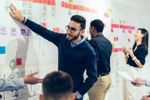 Junges Team arbeitet in agilem Projekt mit Post-its an Whiteboard