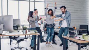 Junges Team freut sich und tanzt am Arbeitsplatz, positive Gefuehle