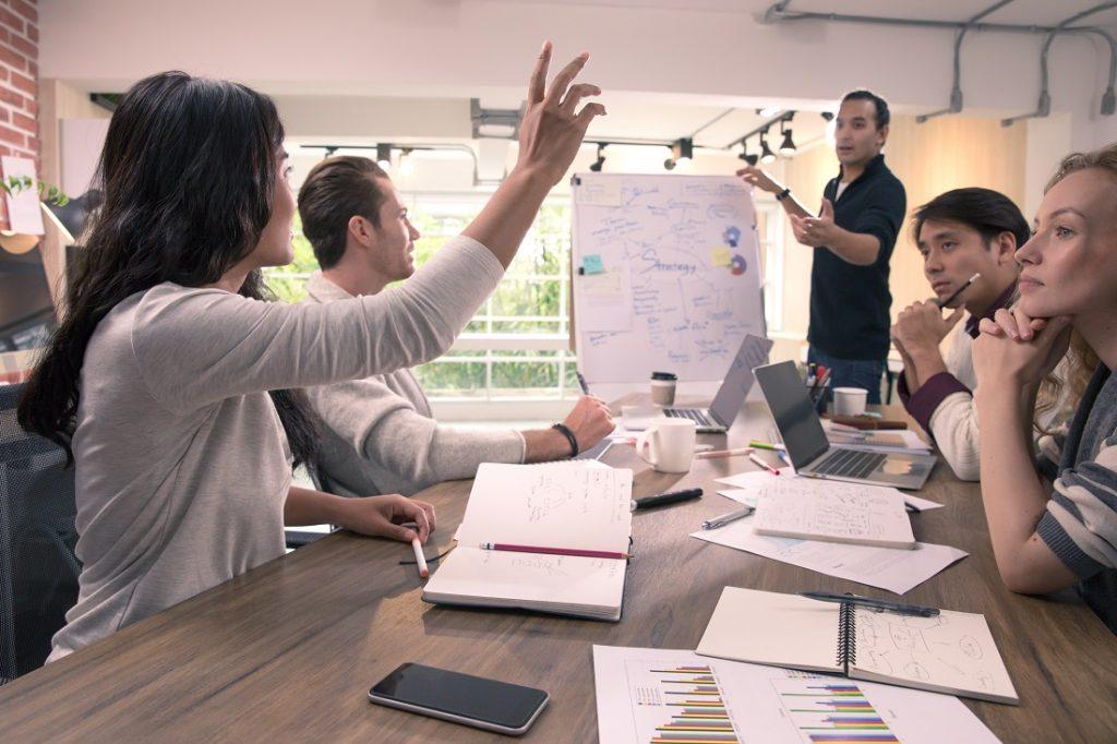 Projektbesprechung in einem Meetingraum mit fuenf Teilnehmer:innen