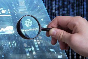 """Hand mit Lupe stellt """"Transparenz"""" in den Fokus, im Hintergrund blauer Bildschirm"""